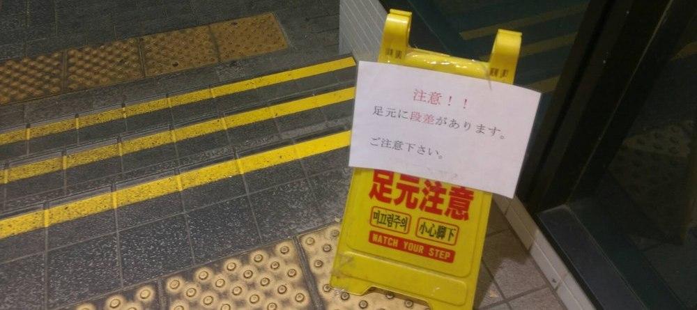 """Pancarte indiquant de faire attention à l'escalier. """"足元注意"""" ashimoto chûi : faites attention à ne pas tomber (littéralement """"à vos pieds"""")"""